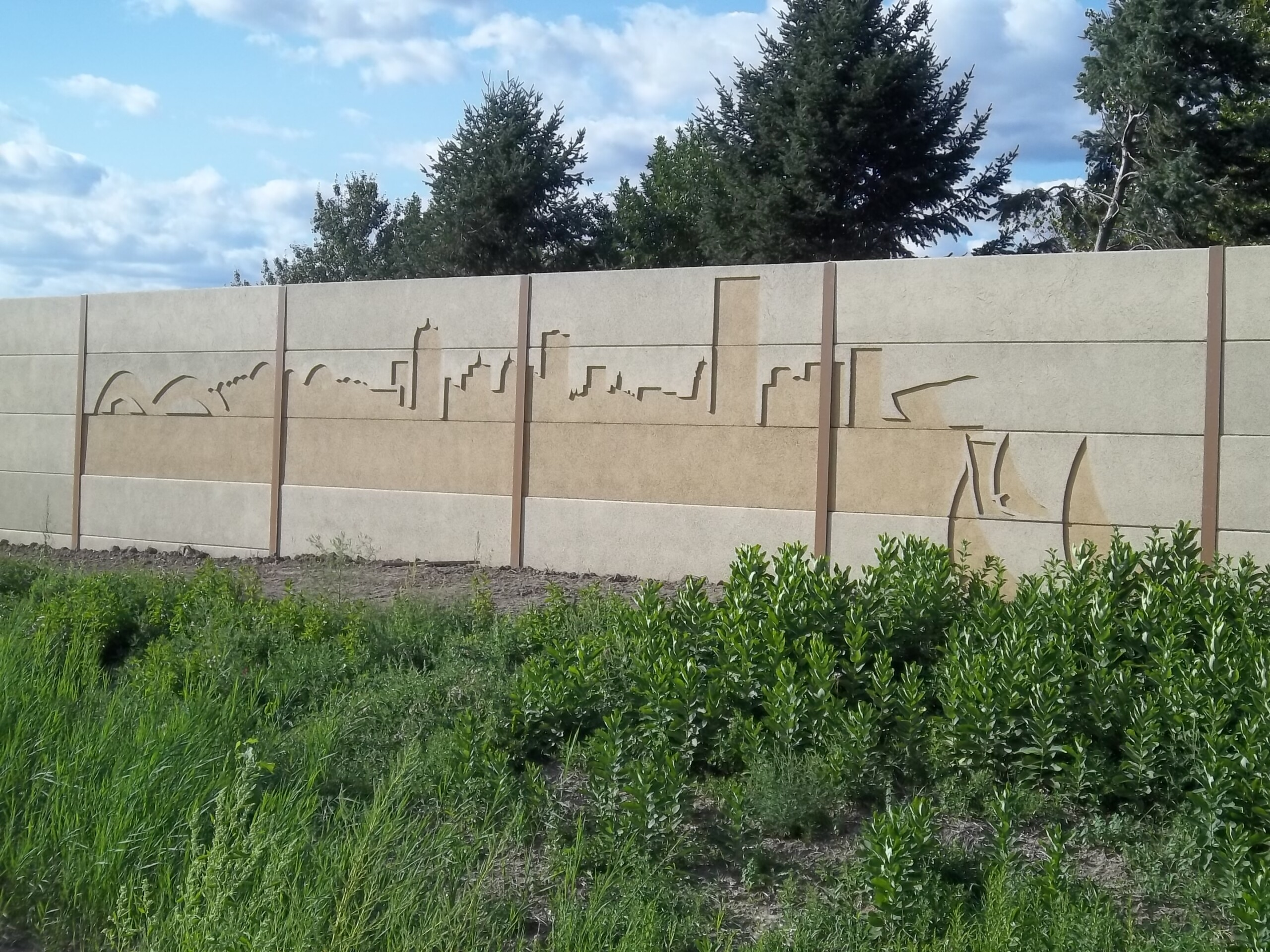 A precast noise barrier featuring a custom cityscape mural along I-94 in Milwaukee, WI.