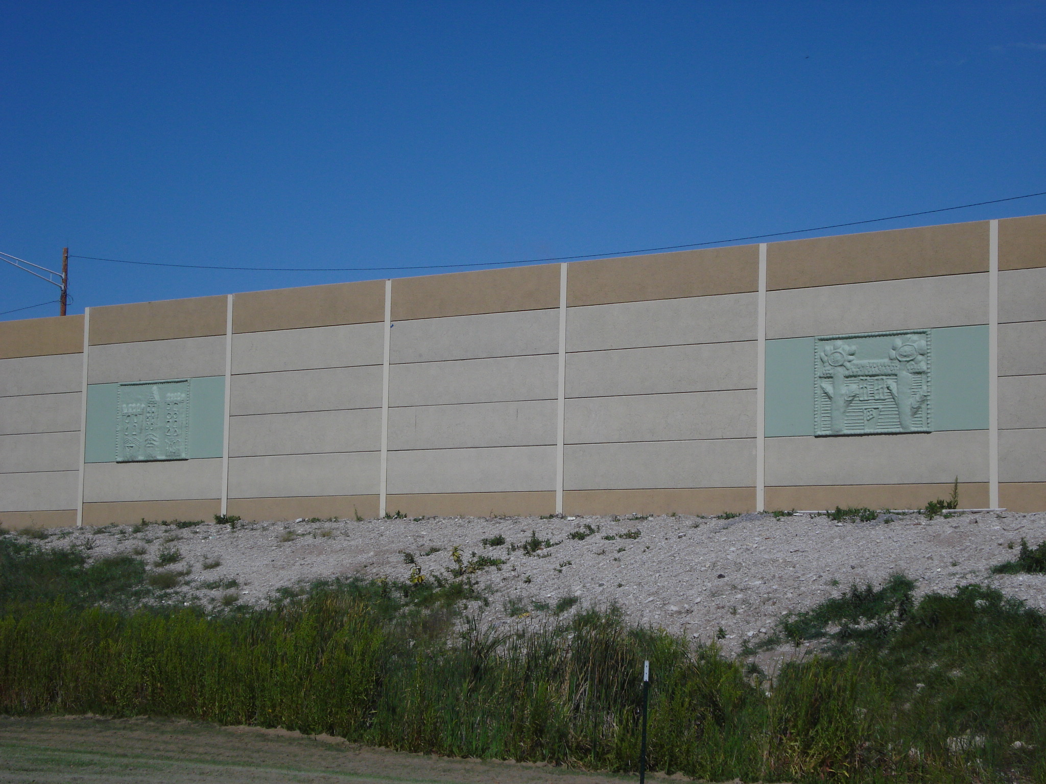A precast noise barrier featuring custom panels created from children's drawings along I-94 in Milwaukee, WI.